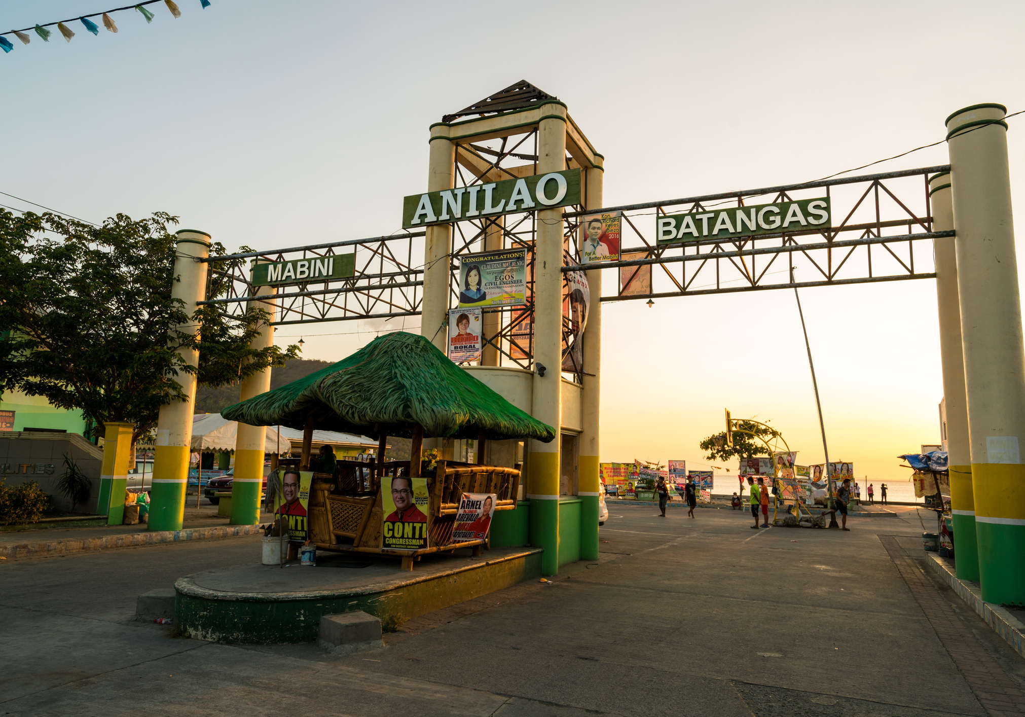 Batangas, Philippines - May 1, 2016: View of the city arch in Anilao in Batangas, Philippines during sunset. People can be seen walking around the street. The sea can be seen upon closer inspection.